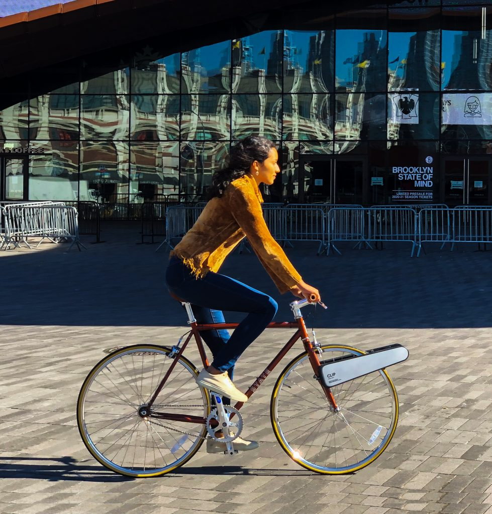 woman riding bicycle with Clip.Bike product attached to front wheel