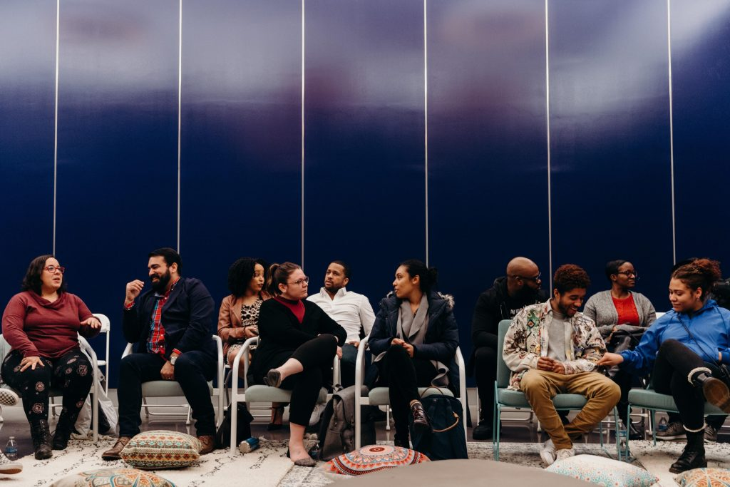 People sitting in chairs and conversing at an event.